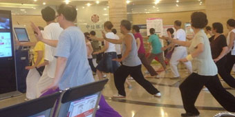 Middle Aged Chinese People Practice Tai Qi inside Bank, Onlookers Confused